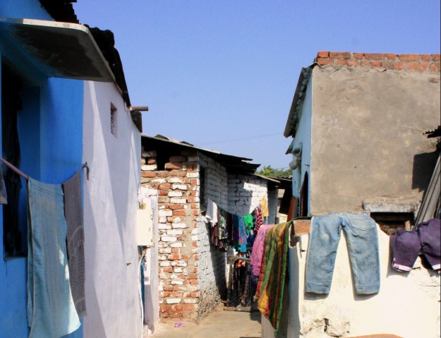 Clothes are hung out to dry on the external walls of houses in the hot afternoon sun. Alleys become an extension of the house and the space is often used to dry clothes, and store household goods.