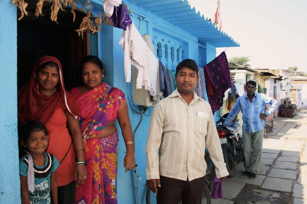 A family stands proudly outside their newly-painted home with their recently acquired motorbike in the background.