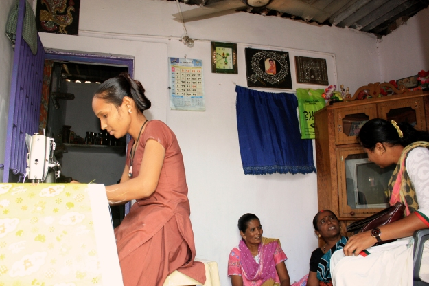 Kinnariben (far right) discusses savings accounts and RAY with SEWA members, as one of the three SEWA members continues stitching cotton blankets. Most SEWA members operate home-based informal businesses, such as tailoring (above), papad-making, etc.