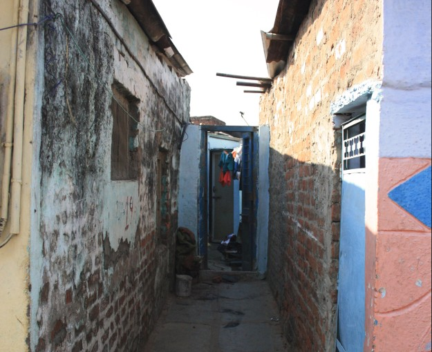 Entrance to a toilet at the end of a narrow alleyway. Implementation of the SNP brought water and sewerage connections, and toilets for individual households, thereby eliminating daily trips to common outdoor and unhygienic toilets. Private toilets have significant implications for women's safety.